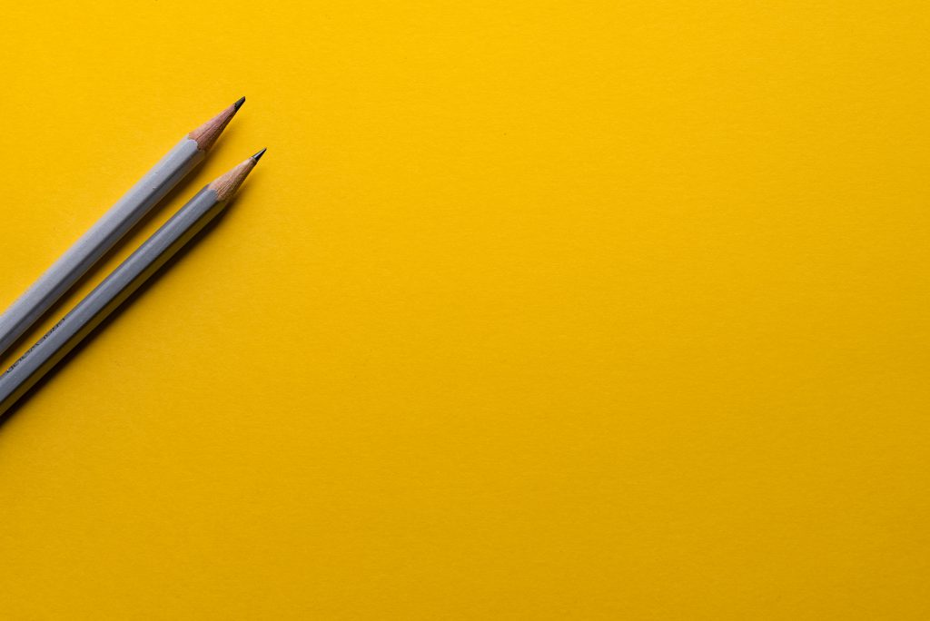 Two sharpened grey pencils laying on a yellow surface.