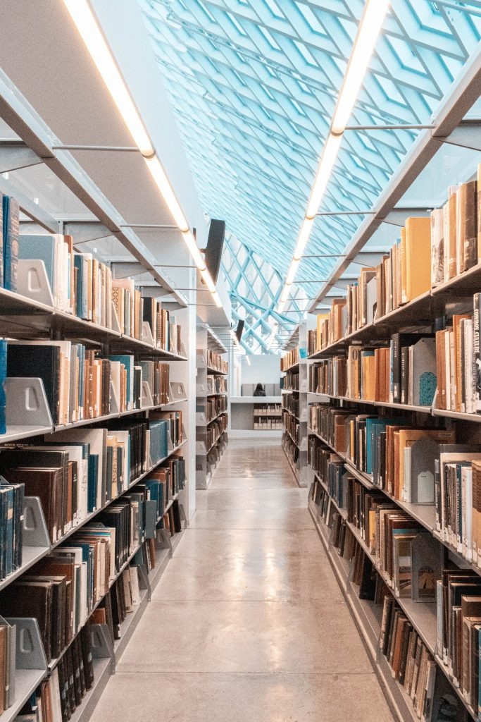 View down a set of library stacks, with a glass and metal roof overhead that lets in lots of natural light.